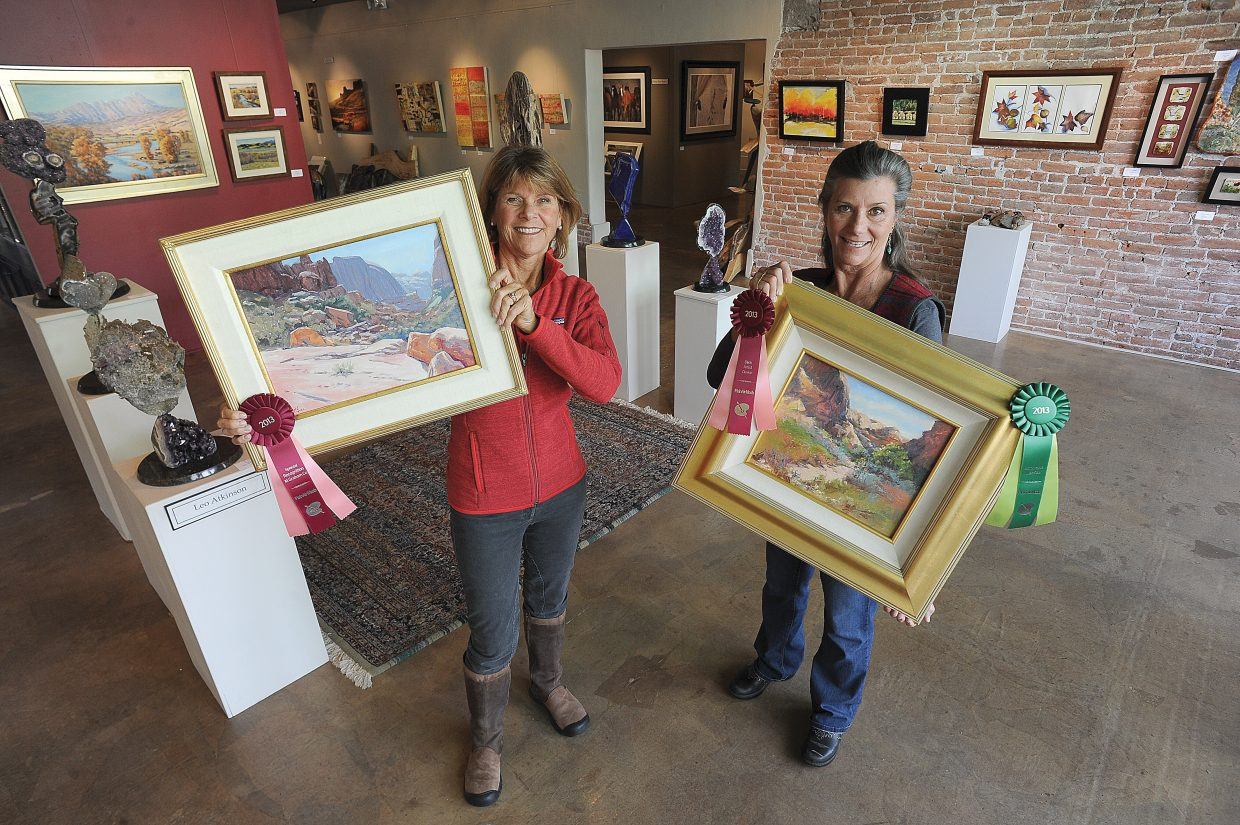 Local artist Bonnie McGee, left, and Susan Gill Jackson hold up their work inside the Circle 7 Fine Art gallery in Steamboat Springs.