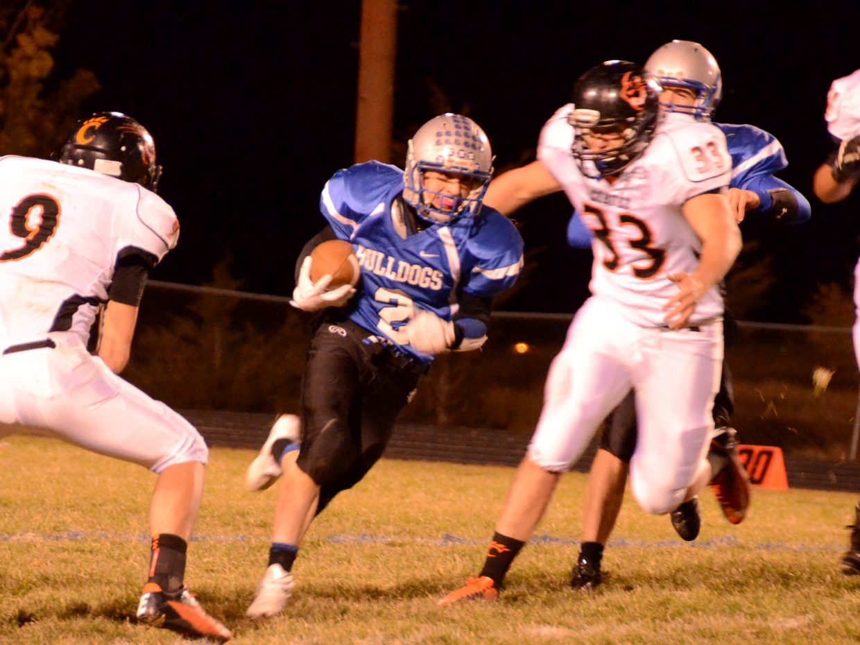 Brayden Peterson cuts between a pair of Montezuma-Cortez defenders Friday night in Craig. Peterson rushed for over 100 yards in the game, but Moffat County fell to the Panthers, 41-21.