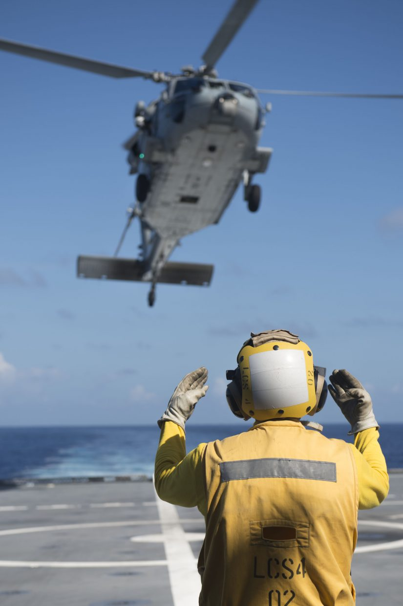 Chief Petty Officer Jed May, stationed with littoral combat ship USS Coronado (LCS 4), directs an MH-60 helicopter assigned to Helicopter Sea Combatant Squadron 14 as it lands during Rim of the Pacific 2016. Twenty-six nations, more than 40 ships and submarines, more than 200 aircraft and 25,000 personnel participated in RIMPAC from June 30 to Aug. 4 in and around the Hawaiian Islands and Southern California.