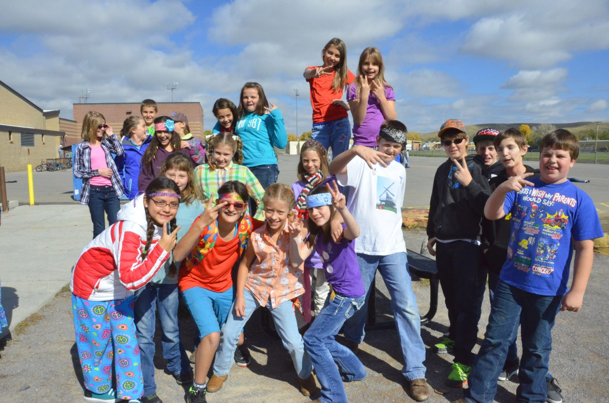 The students of Craig Middle School flash a peace sign during the school's Homecoming week Dress Like a Hippie or Redneck Day Wednesday afternoon.