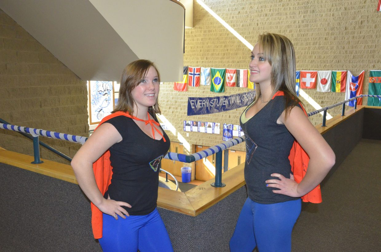 Moffat County High School junior Jodi Hough, left, and sophomore Bailey Baker look to the skies dressed as Supergirl during Homecoming week's Superhero/Supervillain Day.