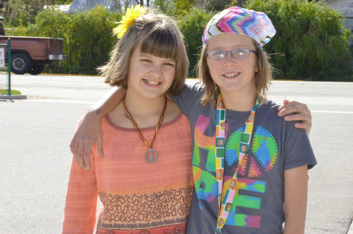 Craig Middle School sixth-graders Raeanna Scott, left, and Mackenzie Smith dress as flower children for CMS Homecoming week activity Dress Like a Hippie or Redneck Day Wednesday afternoon.