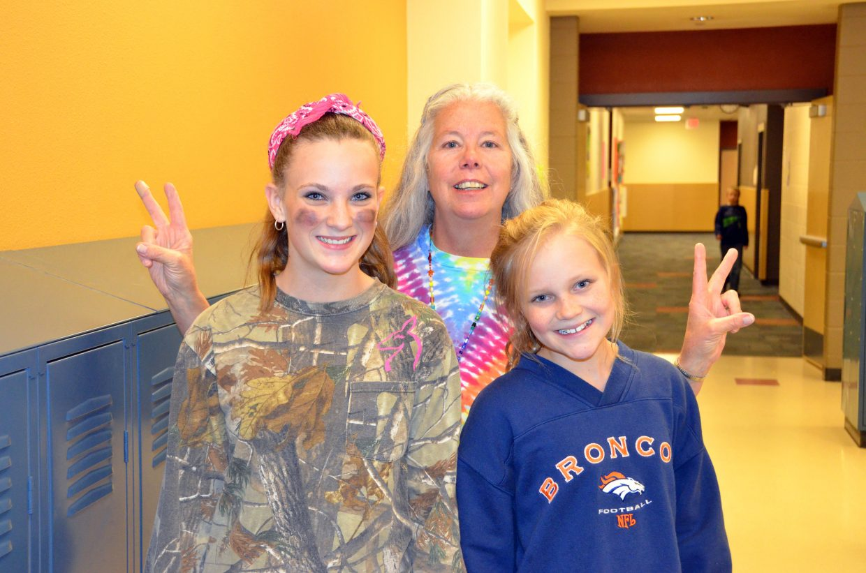 Craig Middle School secretary Beth Gilchrist, center, joins CMS seventh-graders Lacey Wiseman, left, and Caroline Riley to wish people peace as part of the school's Homecoming week Dress Like a Hippie or Redneck Day.