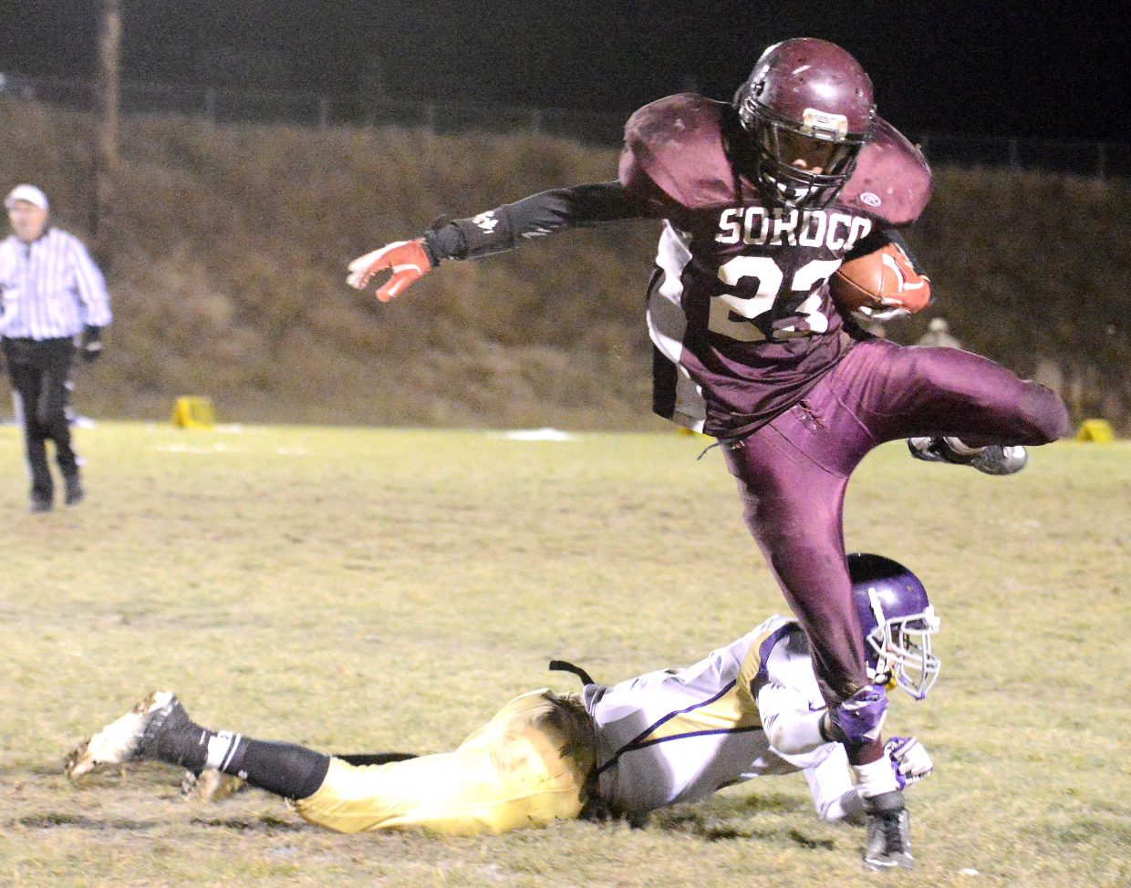Soroco's Carl Rossi leaps over West Grand's Case Gore on Friday to pick up a first down on a fourth-down play.