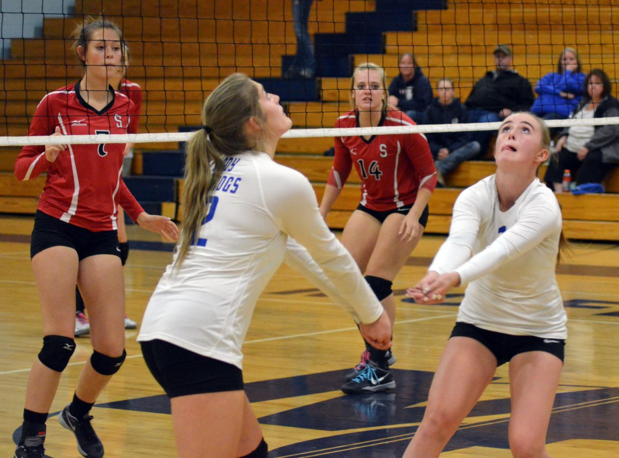 Moffat County High School varsity volleyball players Morgan Nelson (12) and Bailey Lawton (1) get under the ball as Steamboat Springs' Maddie Heydon (7) and Avery Harrington (14) move into action Monday night in Craig. The Sailors won, 3-0, over the Lady Bulldogs.