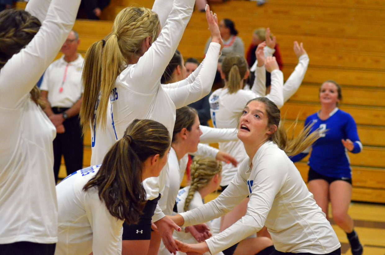 Moffat County's Morgan Nelson exchanges high-fives with teammates during the pre-game warmup Monday night in Craig.
