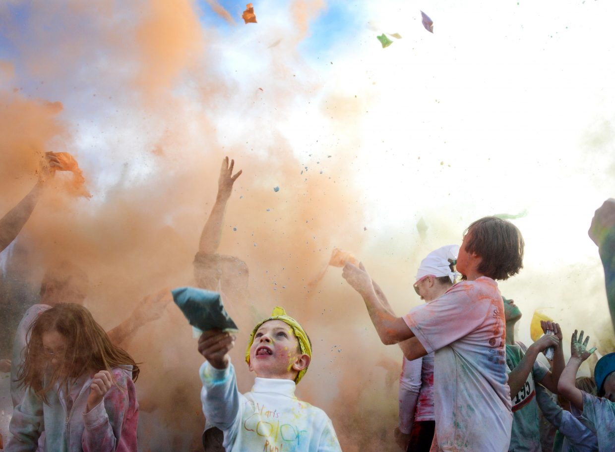 A young runners throws his packet of colored cornstarch into the air on Saturday at the Color Fun Run in Steamboat Springs.