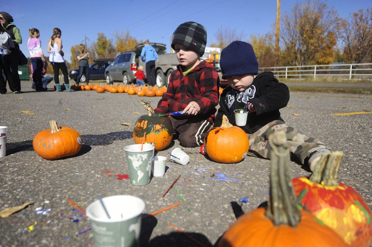Lucas Himmerite, 3, left, paints a pumpkin with his 1-year-old brother Seth on Saturday during the free Pumpkin Festival held by the Steamboat Springs Optimist Club.