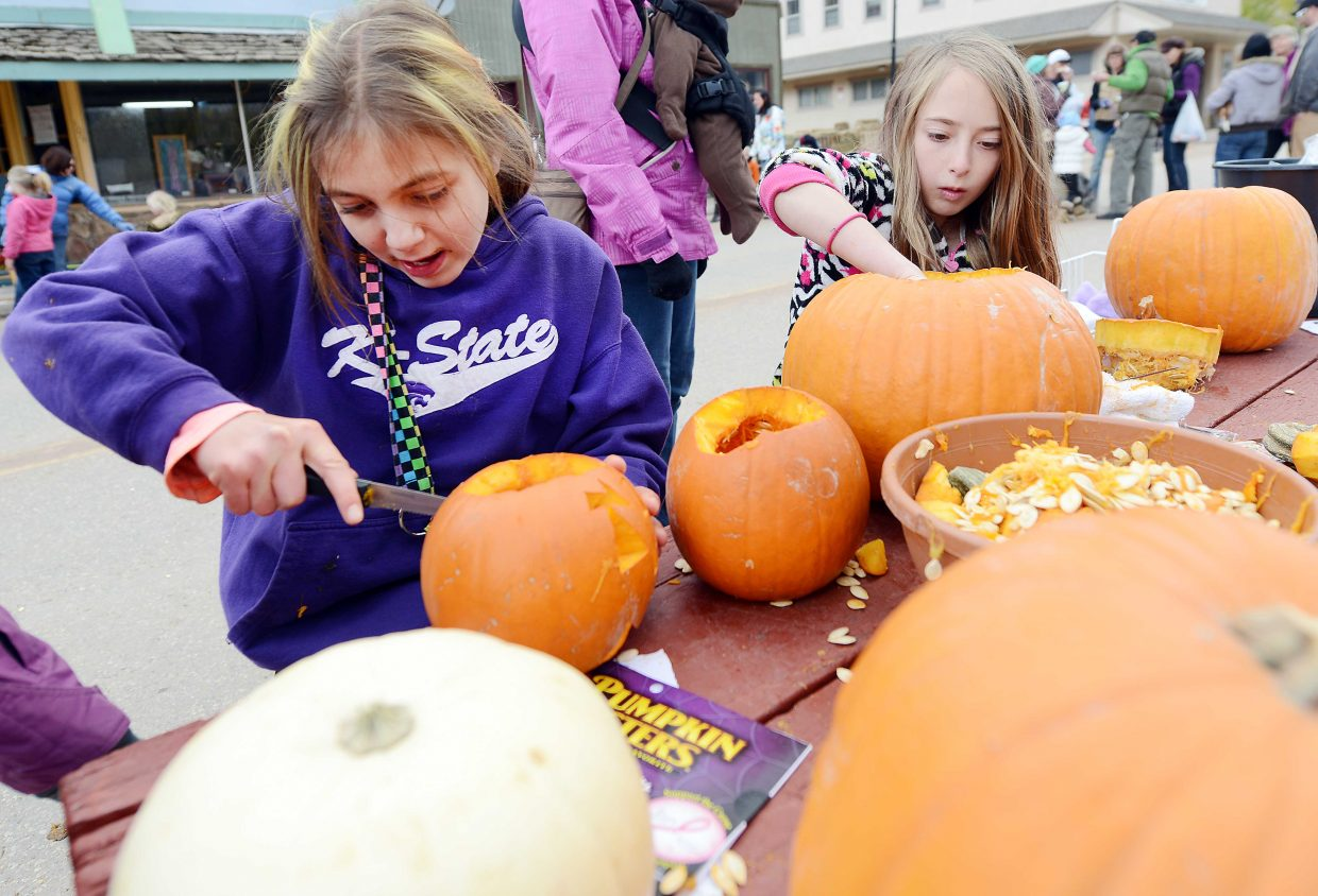 Sophia Benjamin, 9, left, and Alena Switzky, 9, carve pumpkins at the Pumpkin Festival in Oak Creek on Sunday afternoon. The town closed down the main drag and set up hayrack rides, pie-eating contests and pumpkin carving stations.