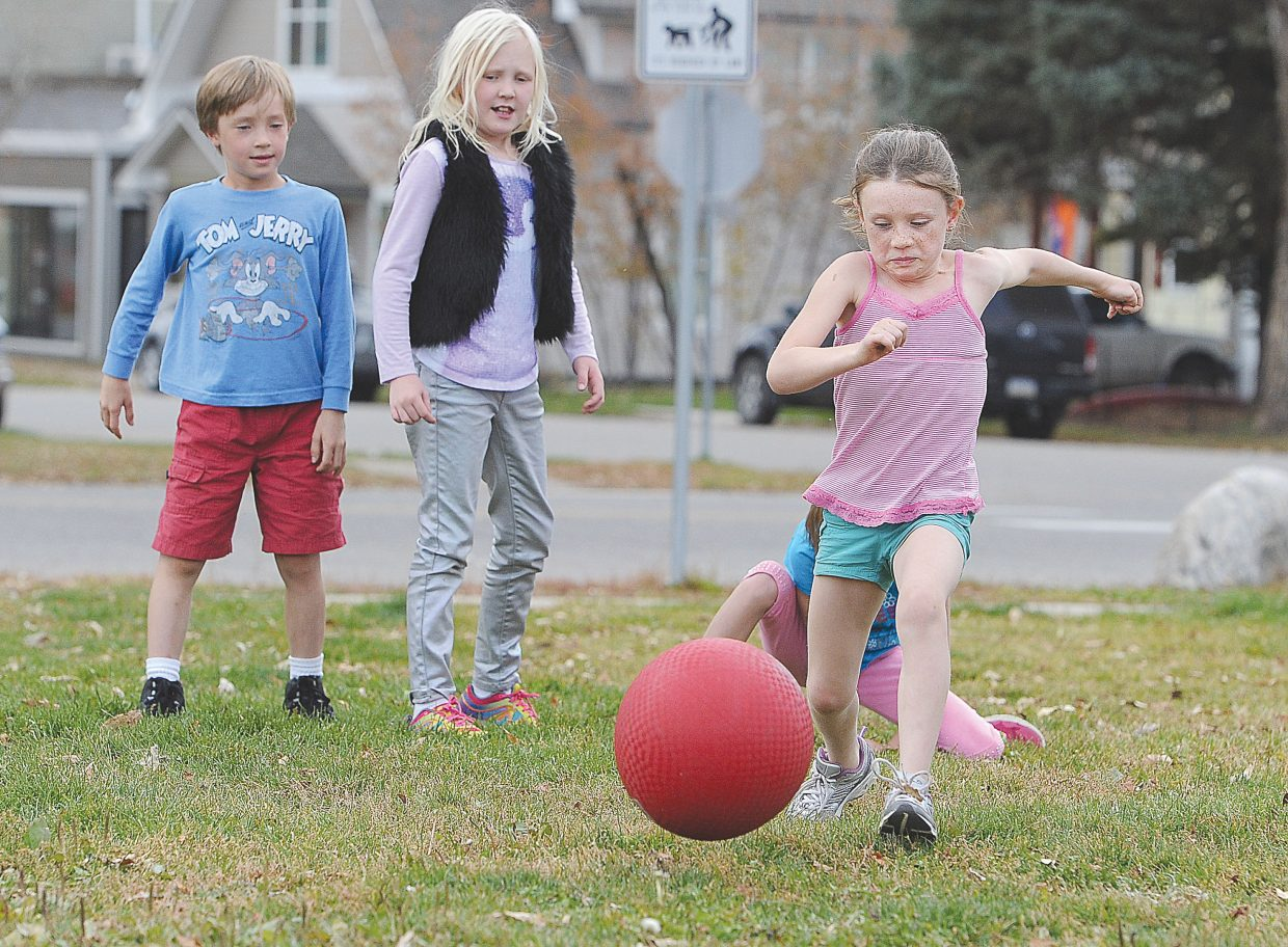 Emerald Mountain School student Scarlet Pepin drives the ball down the third-base line during a game of kickball Monday afternoon outside the George P. Sauer Human Services Center on Seventh Street.