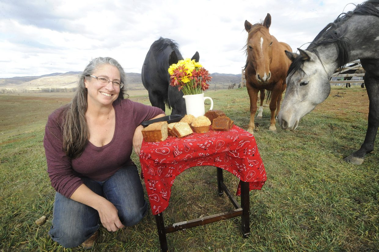 Lisa Larkin, surrounded by her horses on her ranch north of Steamboat Springs, poses next to a table of her chocolate chip pumpkin bread, blueberry streusel muffins and zucchini pineapple bread. Larkin runs Buckin' Horse Pantry from her ranch and sells her breads and sweets on the Community Agriculture Alliance's online ag marketplace.