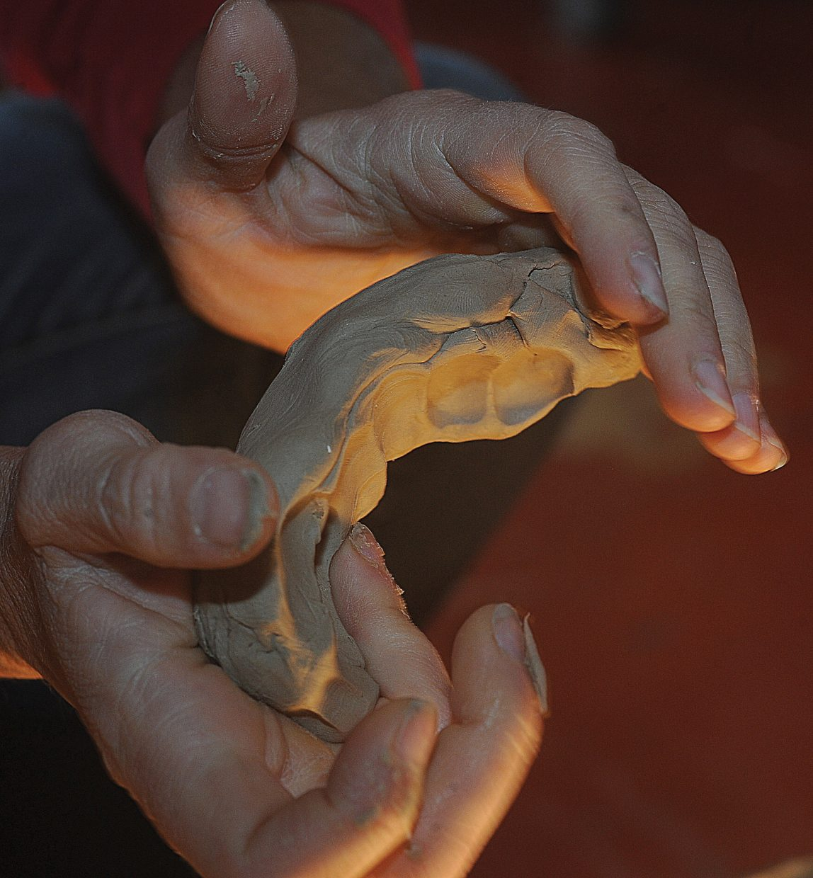 """Sandy Graves uses her hands to shape the clay that she will use to create her next bronze sculpture. """"This is why I'm a bronze sculptor,"""" Graves says. """"I chose this medium because I like working with the clay. It's elastic, and it's forgiving."""""""