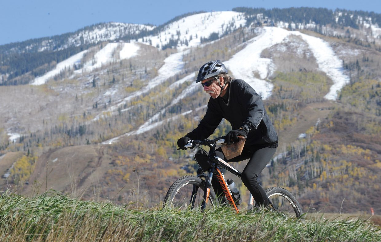 Steamboat Springs resident Steve Rapp takes advantage of the warm weather as he rides along the Yampa River Core Trail on Tuesday afternoon with the snow-covered slopes of Steamboat Ski Area forming the perfect backdrop.