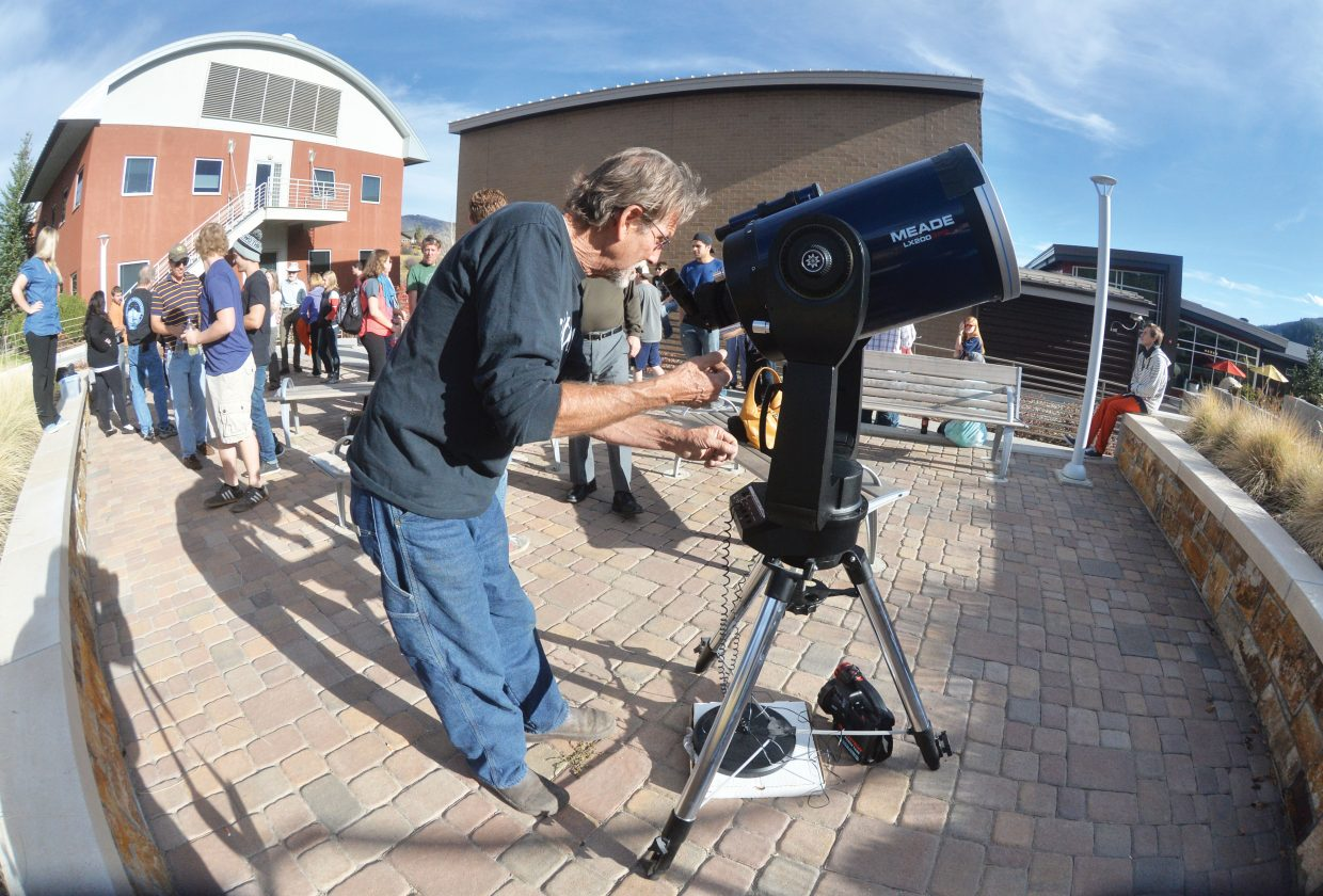 Herb Roehrs adjusts a telescope with a special filter on it that allowed people to view the partial solar eclipse Thursday afternoon outside the new Academic Center on the Colorado Mountain College's Alpine Campus. Crowds showed up to view the celestial occurrence.