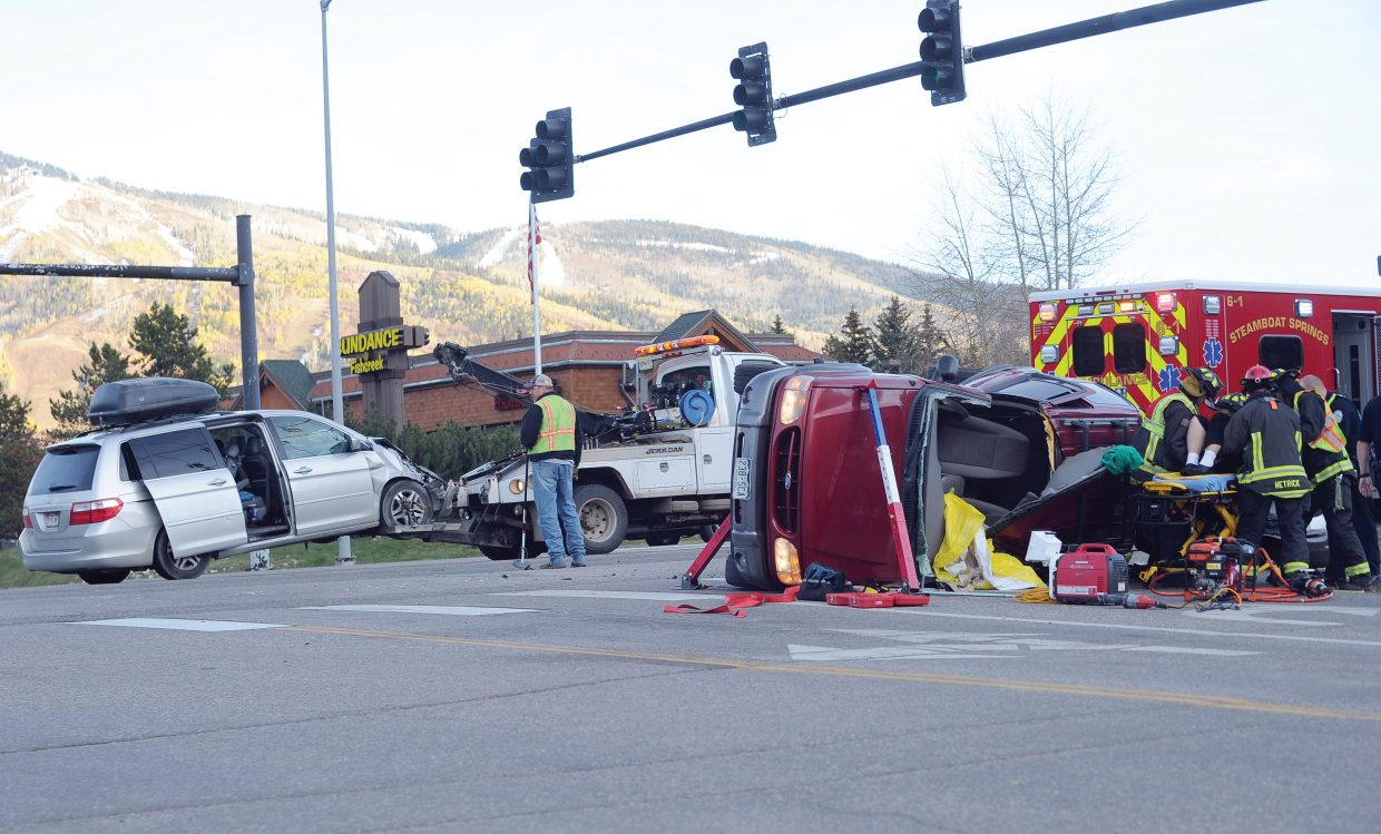 Members of Steamboat Springs Fire Rescue work to remove a person from a Ford SUV at Anglers Drive and U.S. Highway 40 on Thursday evening after a two-car accident. Eastbound traffic was rerouted onto Anglers Drive for about an hour while the accident was cleaned up.