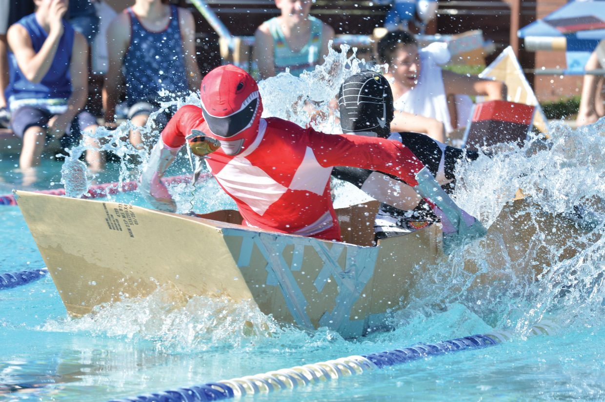 Steamboat Springs High School seniors Sam Meyer, front, and Ian Caragol race across the Old Town Hot Springs pool Friday morning during the Cardboard Classic. The races featured physics students and their vessel from Steamboat Springs High School and South Routt.