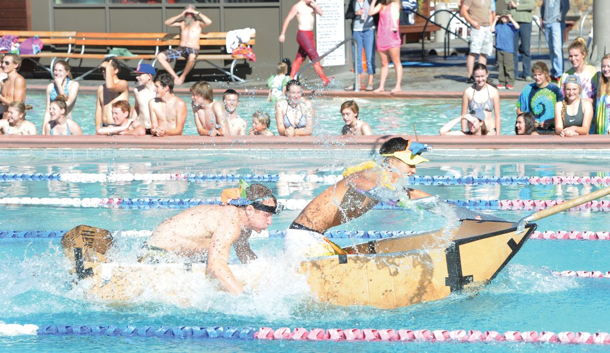 David Kidd, front, and Devin De Jong race across the Old Town Hot Springs pool to victory Friday morning during the Cardboard Classic. The races featured physics students and their vessels from Steamboat Springs High School and South Routt.