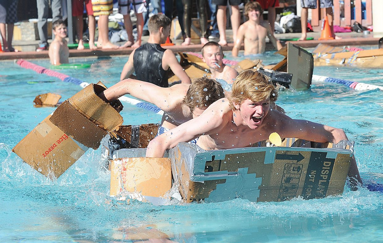 Peter White, front, and Andrew Firestone power across the Old Town Hot Springs pool Friday morning en route to winning the cardboard classic boat race. The race features physics students from Steamboat Springs racing homemade cardboard boats across the pool while learning the fundamentals of physics. The students designed the watercrafts in Eric Nilsson's physics class and raced them as part of an exam.