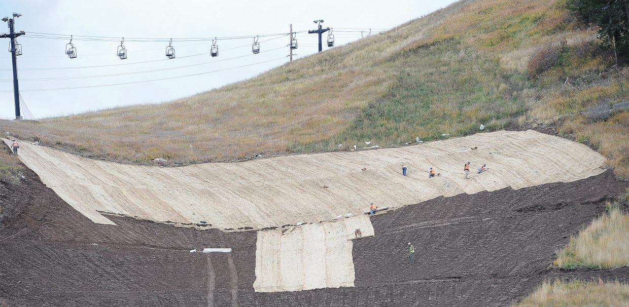 Crews work to place erosion control fabric, which will hold, and re-validate the face of Howelsen Hill, following a spring mudslide in 2014.