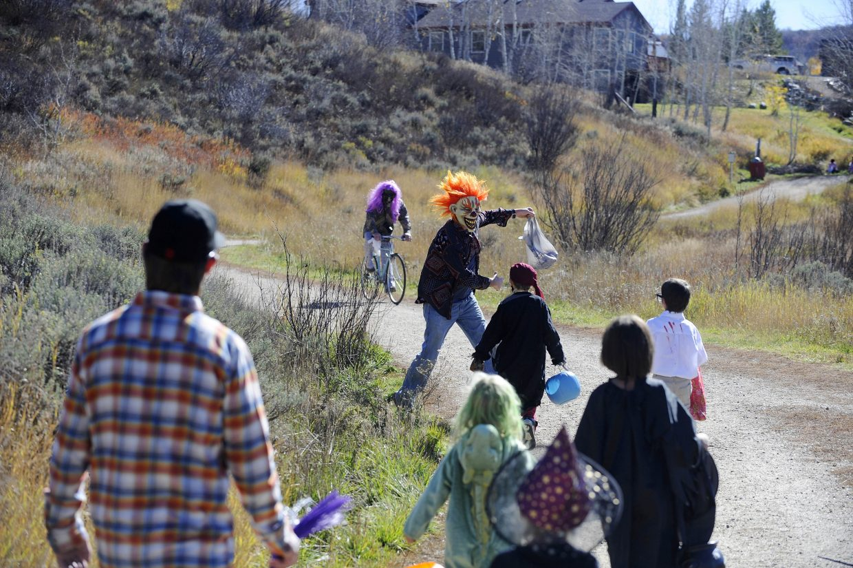 Parent Ross Riser scares the kids during their hike Saturday along Butcherknife Trail.