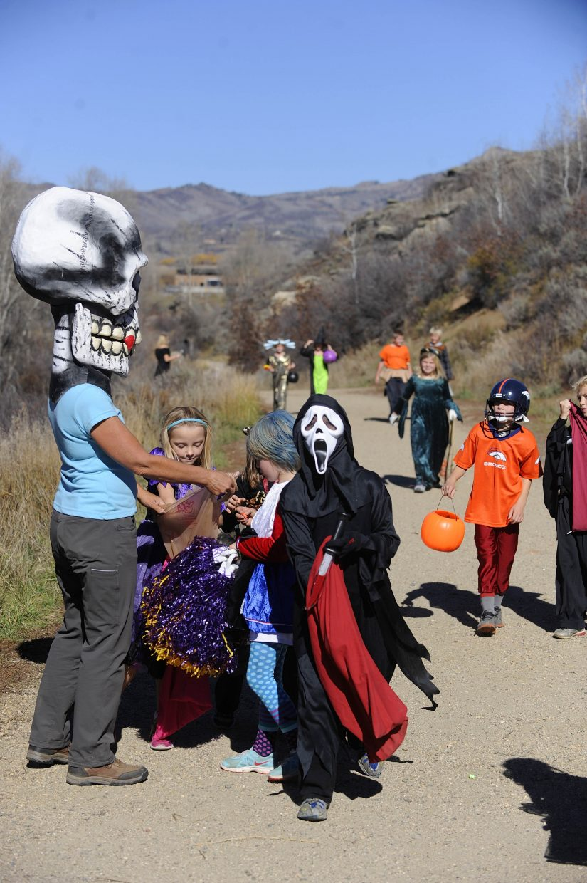Second-graders pick up candy during a hike along Butcherknife Trail.