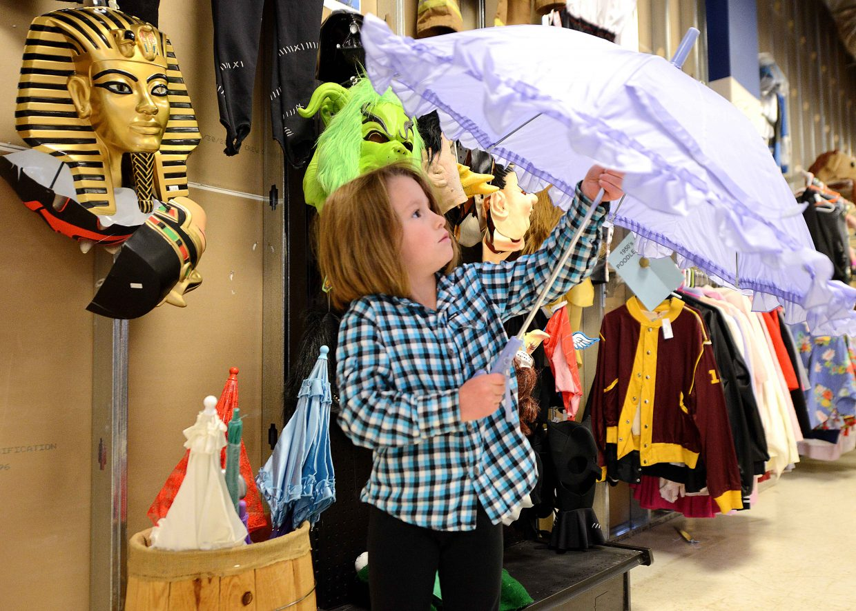 Mya Chase, 5, examines a purple parasol Sunday while searching for a Halloween costume in Steamboat Springs. The holiday is looming and will close down Lincoln Avenue on Thursday as hundreds of children and adults don costumes and fill the street from 5 to 7 p.m.