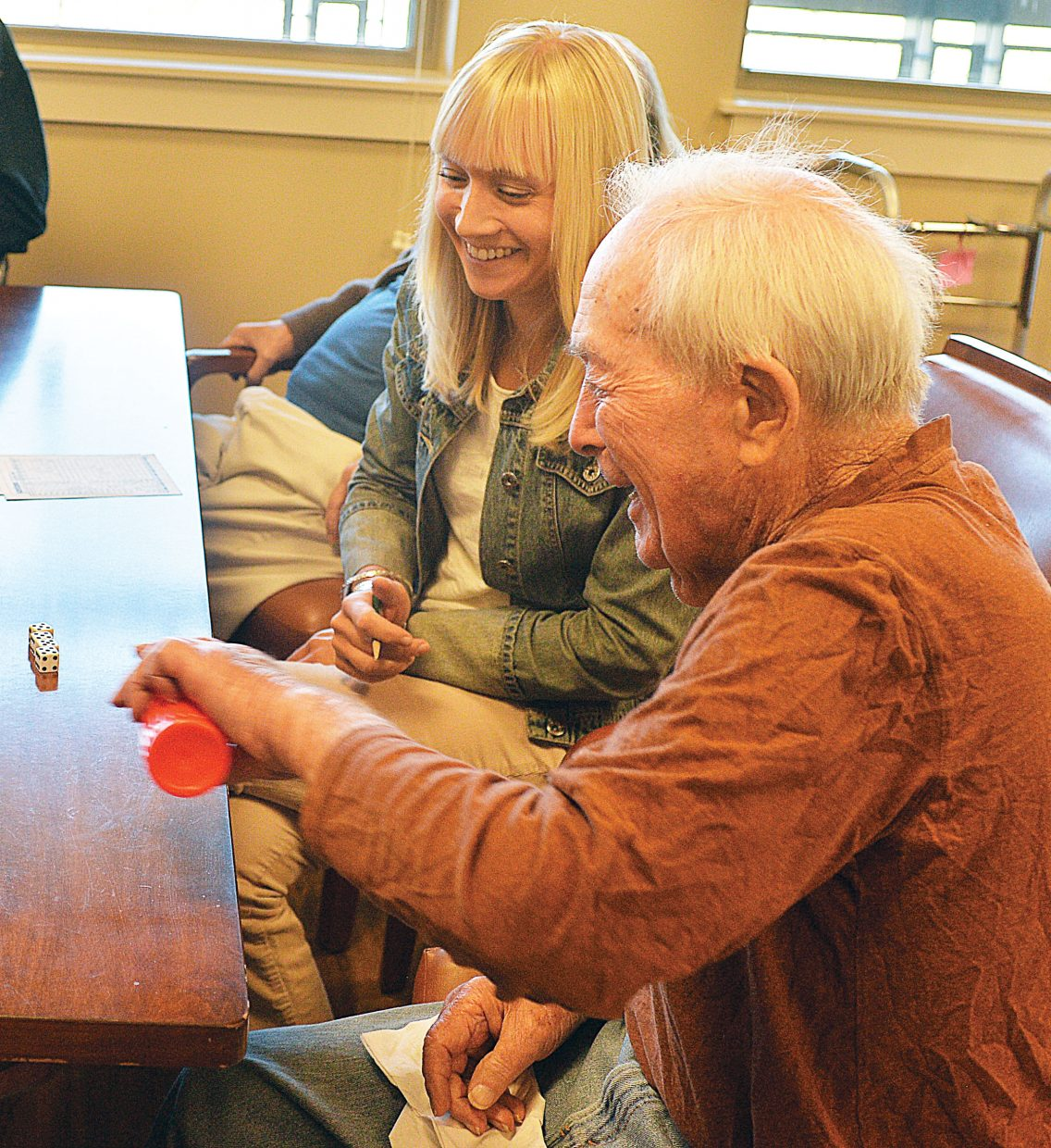 Stan Whittemore, a Casey's Pond Senior Living resident in the Harbor, plays a game of Yahtzee with other residents and Community Lives Coordinator Laura Oslowski.