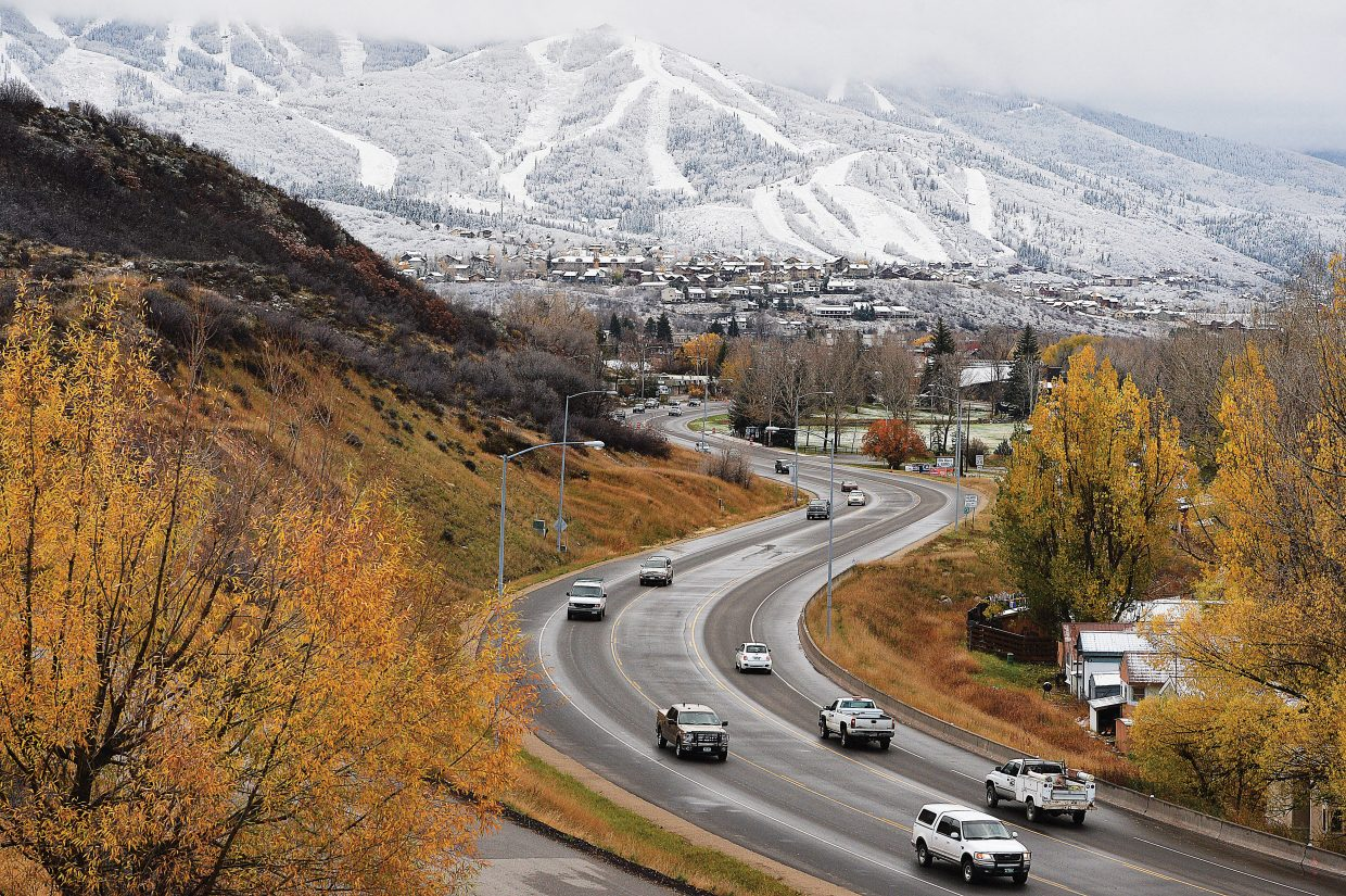Traffic moves along the wet pavement of U.S. Highway 40 on the west side of Steamboat Springs on Monday morning. A Sunday night storm was more than enough to get the roads wet and even left a touch of snow on the grassy areas in town.