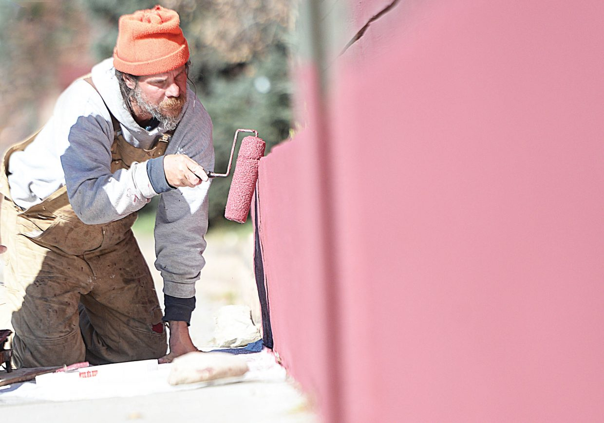 Jay Benton uses a roller to paint the wall outside the Old Town Hot Springs Thursday afternoon. Benton, a mason, repaired and painted the wall with his business partner Fred Castaldo.