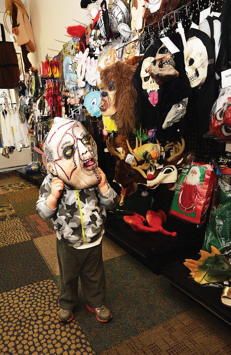 Ryland Kissell checks out the masks at Costume Party in Sundance at Fish Creek Plaza. The business has stocked up on Halloween costumes and is expecting things to get pretty busy the next few days as All Hallows' Eve draws closer. And there will be plenty to do this Friday as locals celebrate the holiday in Steamboat Springs.