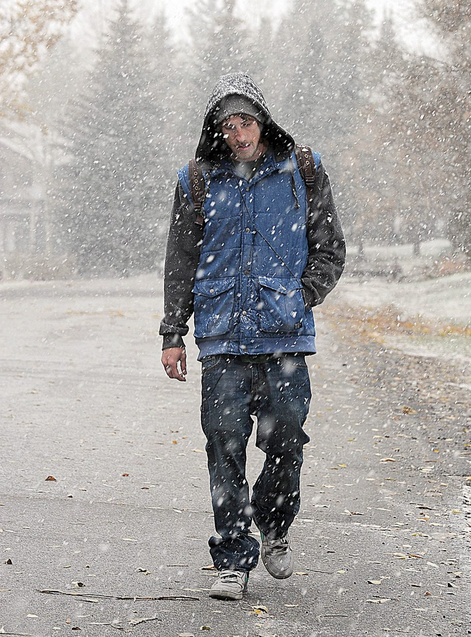 Ozzie Kreckow walks through a steady stream of snow Tuesday morning in downtown Steamboat Springs. The National Weather Service is reporting a chance of snow through Friday with highs in the lower 40s.