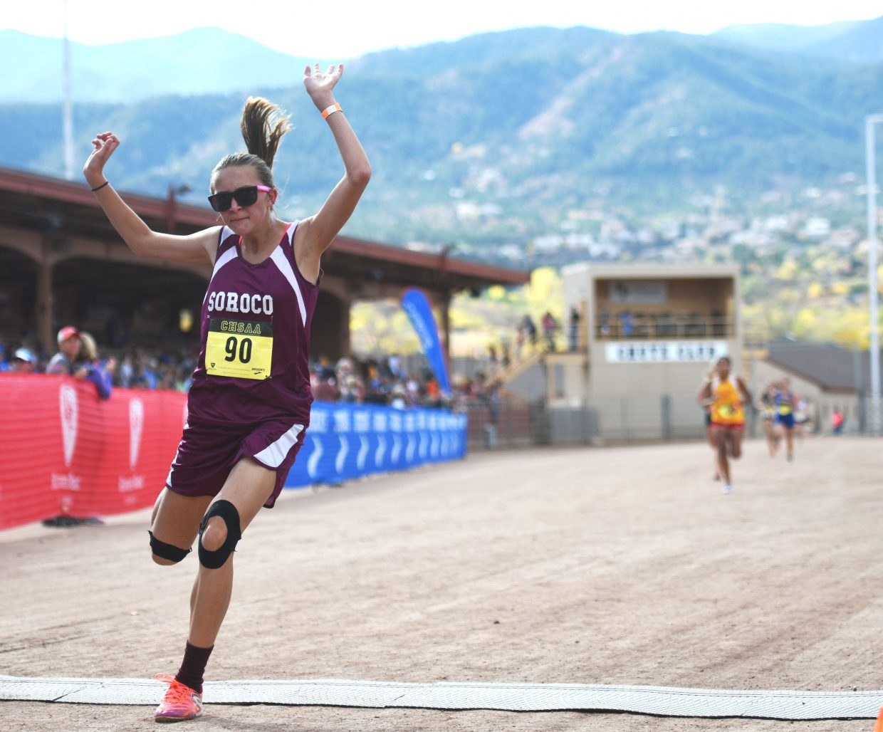 Soroco freshman Kourtney Bruner lunges across the finish line Saturday at the Class 2A state cross country meet in Colorado Springs.