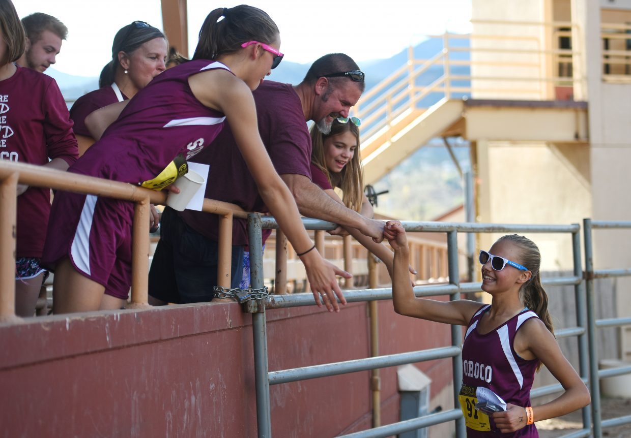 Chloe Veilleux celebrates with her friends and family after winning the Class 2A state cross country championship Saturday in Colorado Springs.