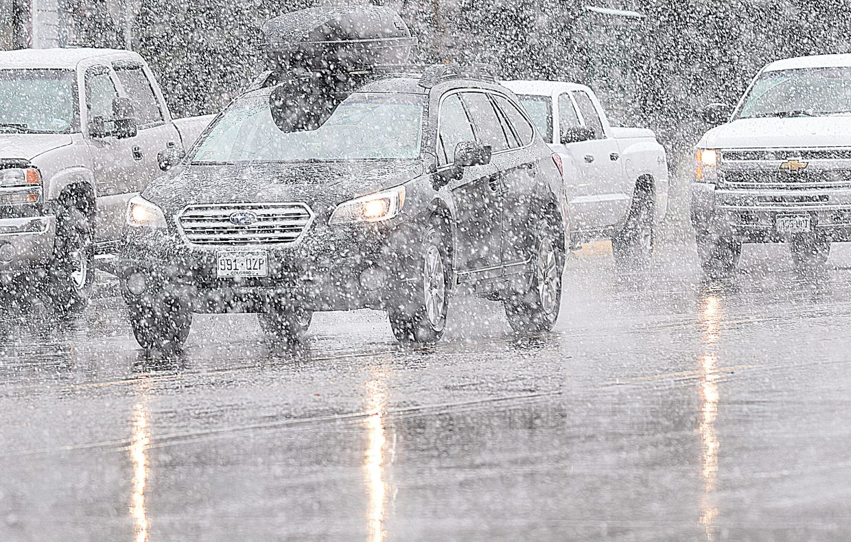 Traffic makes its way through heavy snow around noon Monday in downtown Steamboat Springs. The snow only lasted for a few moments before turning to rain, but the wet, cool weather is a reminder that winter isn't far away.