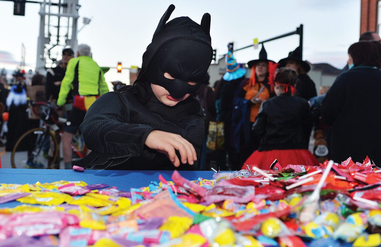Five-year-old Jackson Schutt, aka the Bat Man, grabs a few treats to keep his strength up in order to battle a huge host of evil villains showed up on Lincoln Avenue Friday night for the annual Downtown Halloween Stroll. The annual holiday event drew hundreds of children, and their parents to downtown Steamboat Springs for the chance to pick up a few treats from local merchants.