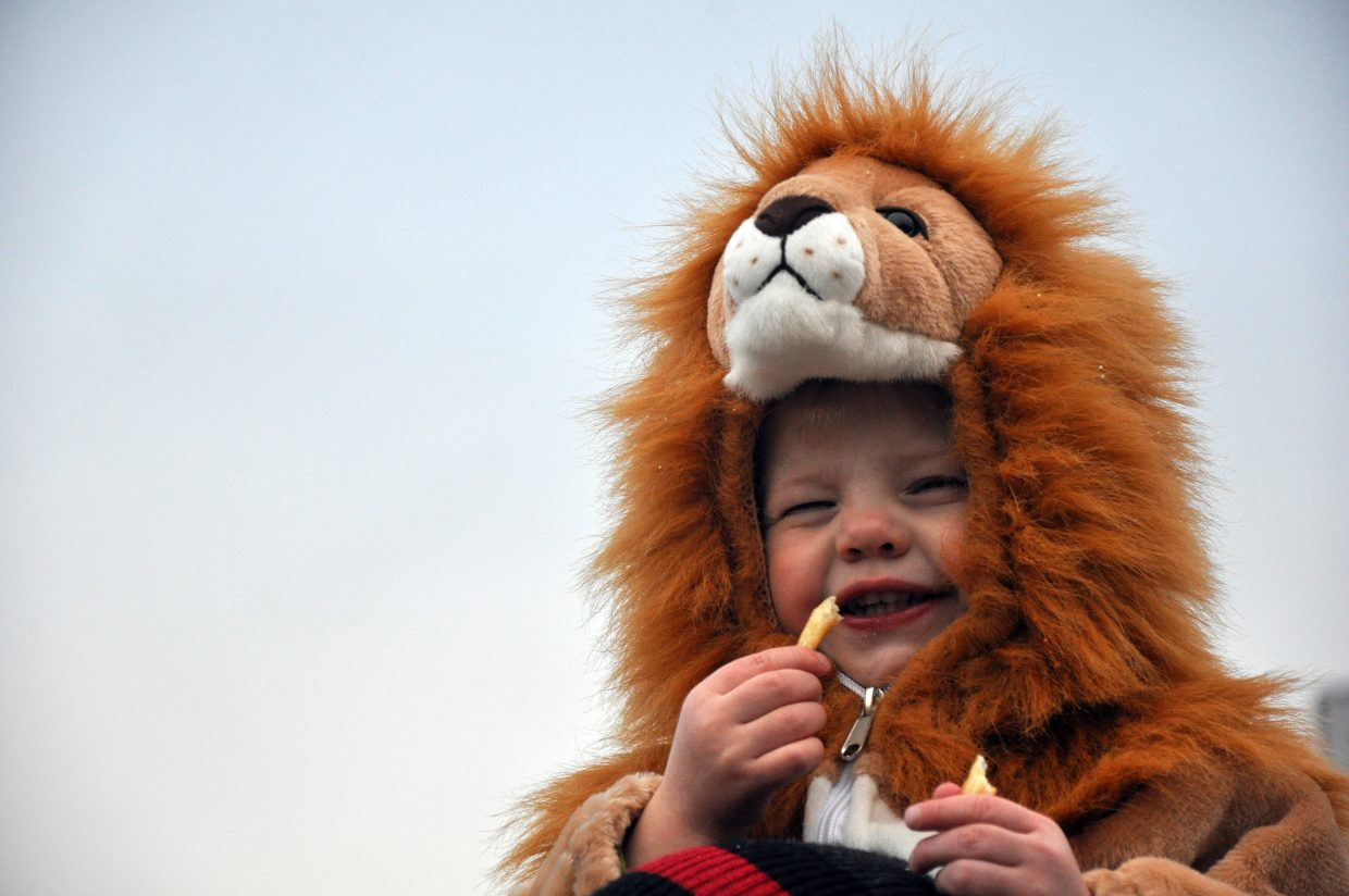 Hank Metcalf enjoys a snack while posing as a lion Thursday night at the Steamboat Springs Halloween Stroll. Hundreds of costume-clad trick-or-treaters went trick or treating downtown.