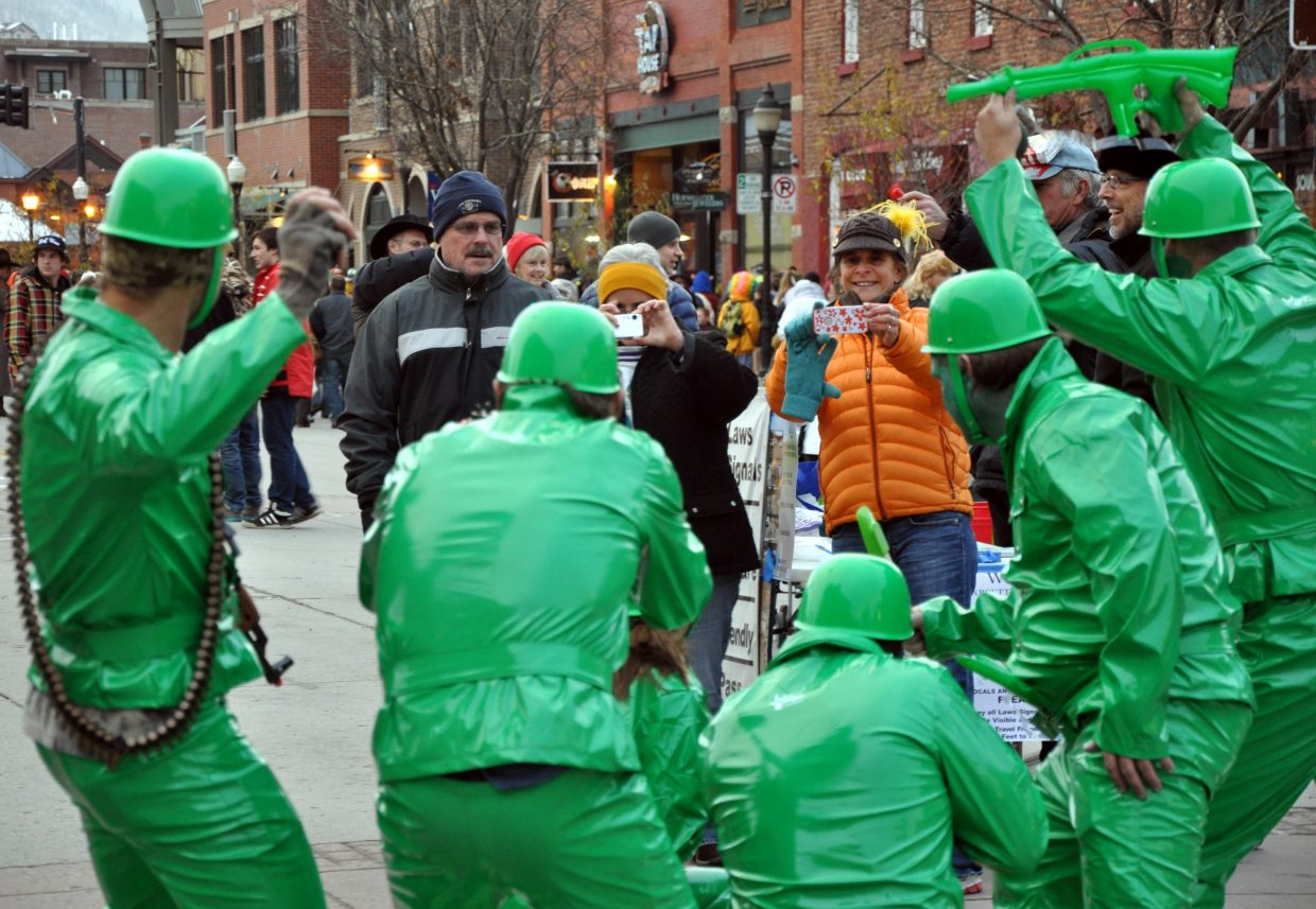 A woman snaps a pick of a squad of green army soldiers on Thursday at the Steamboat Springs Halloween Stroll.