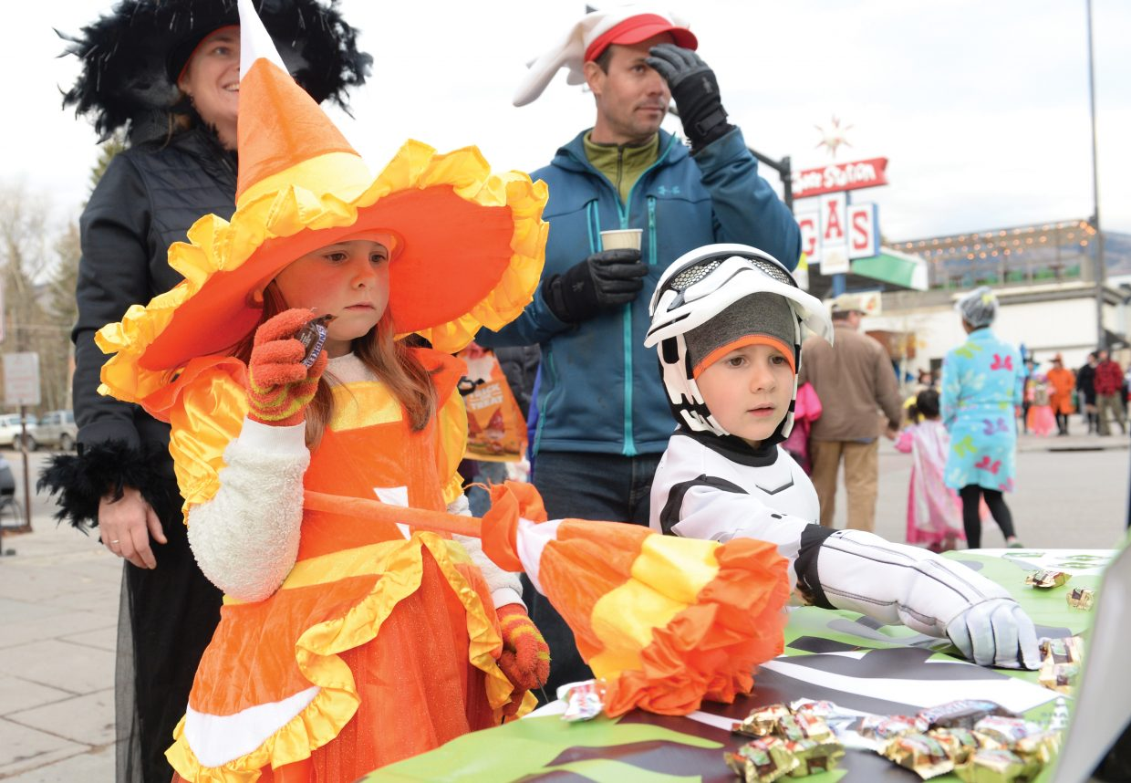 Vivian Sloop, the candy corn witch, and her brother, Otto Sloop, a storm trooper, find a few treats Monday while taking part in the Steamboat Downtown Halloween Stroll.