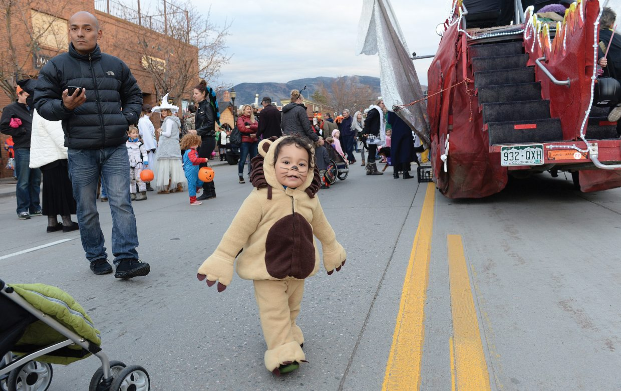 Benjamin Garcia, dressed as a lion, looks for treats Monday while taking part in the Downtown Halloween Stroll.