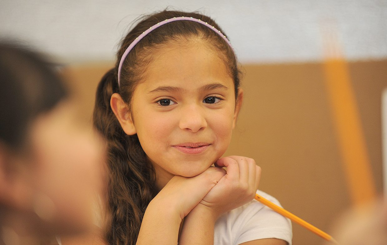 Fifth-grader Ximena Escarcega smiles while working with a friend at the homework club after school at Soda Creek Elementary School. The club is open to all students, but many of the children taking part come from non-English speaking homes.