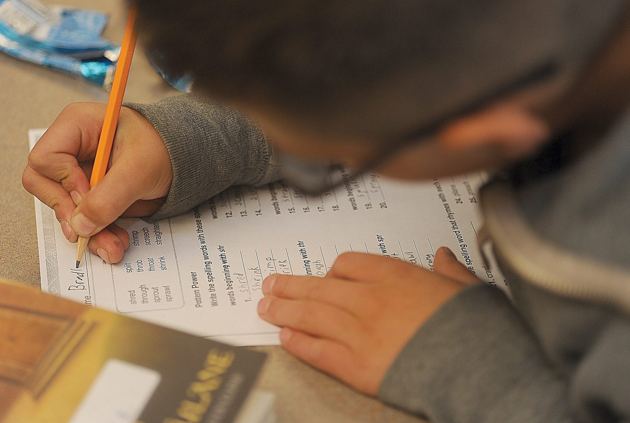 Fifth-grader Melvin Marquez listens to one of the teachers while completing a homework assignment after school at Soda Creek Elementary School.