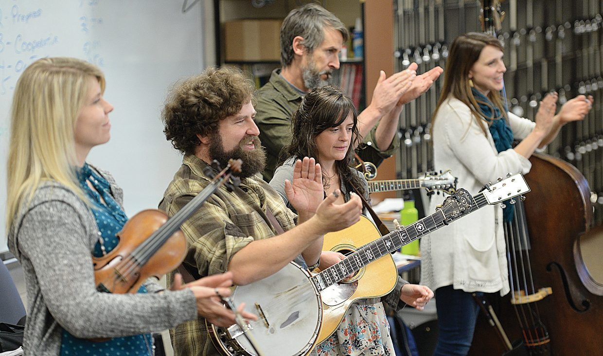 """The Railspiltters, ]from left , fiddle player Christine King; banjo player Dusty Rider, guitar player Lauren Stovall, mandolin player Pete Sharpe and bass player Leslie Ziegler, applaud the seventh-grade band at Steamboat Springs Middle School after a rehearsal Tuesday morning. The band is part of the Strings Music Festival's """"School Days"""" program, which brings professional musicians to Steamboat Springs to present music workshops and conduct rehearsals alongside school music directors and students. Students perform a final evening concert at the end of the second year with the featured musician at the Strings Music Pavilion. The concert is for parents, teachers, friends, students and community members."""
