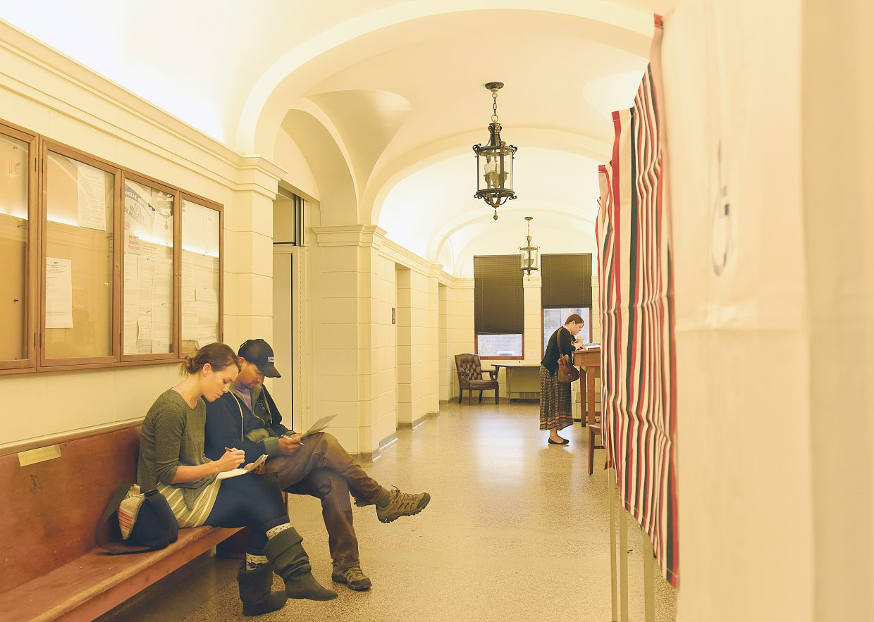Fiava Flores and Mike Giordano vote in the hallway of the Routt County Courthouse Tuesday evening as the 2015 Routt County election entered its final hours. Voters decided the fate of city council and school board candidates and addressed several big issues including whether or not Steamboat Springs would spend $92 million to update existing schools and build a new high school to address overcrowding.