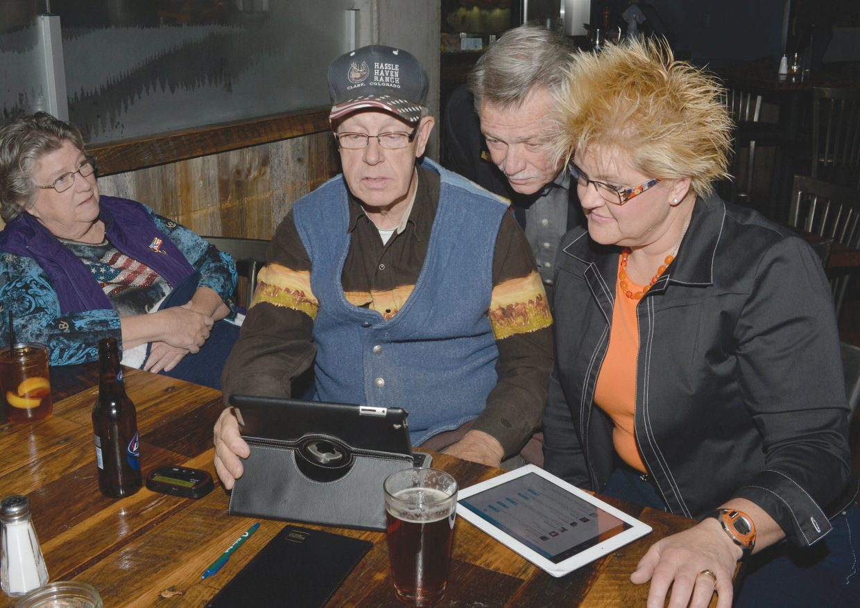 Brita Horn, who was running for Routt County treasurer, and Chuck McConnell, who was running for Colorado House District 26, check returns with Chuck Vale and his wife, B.J. Vale, during a Republican watch party at Carl's Tavern on Tuesday. Horn won the Routt County treasurer's position, but McConnell ended up losing to incumbent Diane Mitsch Bush.