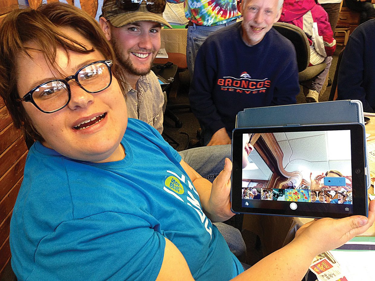 Jamiee Purcell-Sexton shows off one of the new iPads donated to Horizons Specialized Services by Ski Town Computing earlier this week. Tim Beh and client Donnie Pearce are shown in the background. Worthen's company, Ski Town Computing, donated an iPad Air and iPad Mini to Horizons. The iPad Air will be used at Milestones Day Program for educational applications, helping people learn language, math and other skills. The iPad Mini will be distributed through Horizons' Family Support Program to allow for easier communication between a child and his family, teachers and friends.