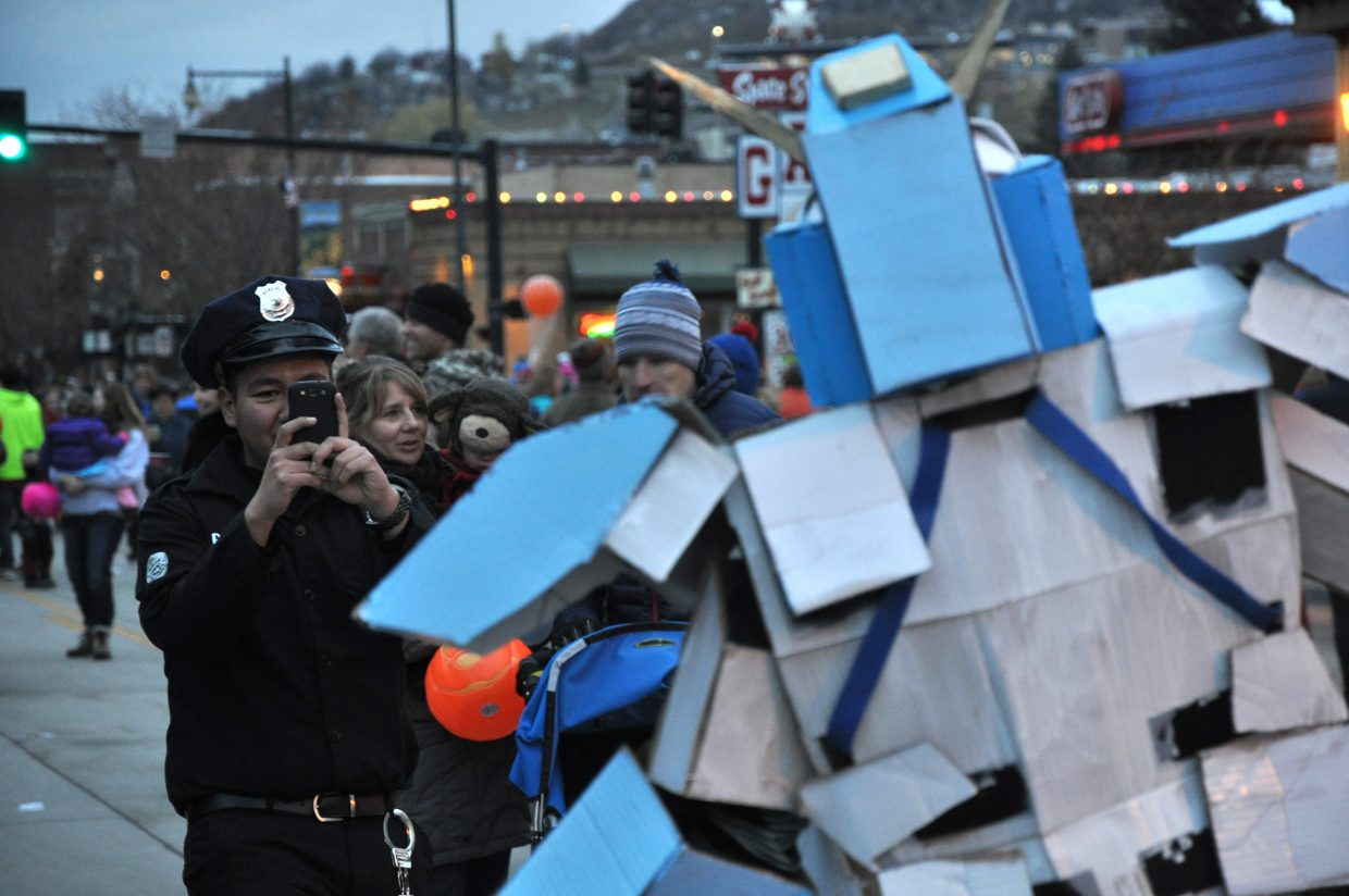 Spectators take pictures of Brandon Temple, dressed as a Japanese robot on Thursday at the Halloween Stroll.