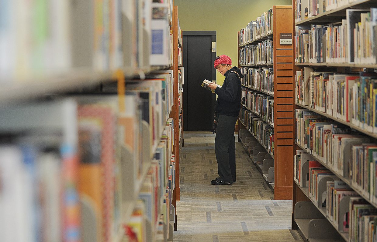 Jaime Wisch checks out the books at Bud Werner Memorial Library on Thursday afternoon in Steamboat Springs.
