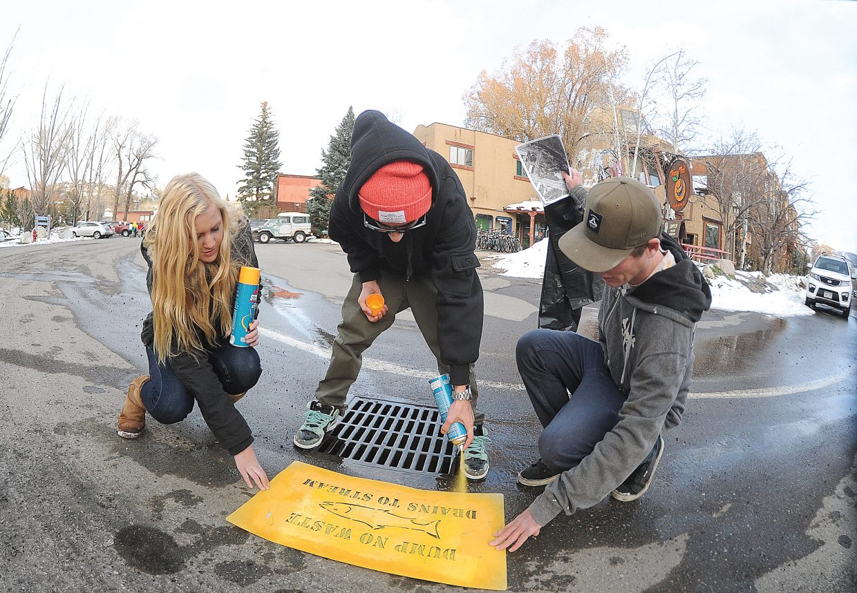 The Lowell Whiteman School students Casey O'Connor, from left, and Alex Ahmad joined Colorado Mountain College student Thomas Stefan Elli on Thursday afternoon to stencil storm drains in Steamboat Springs. The stencils are meant to serve as a reminder to not dump waste into the drains that run into the Yampa River and other waterways in the Steamboat area. Yampatika organized the effort, and most of the volunteers were from Lowell Whiteman where students are encouraged to take part in community service projects.