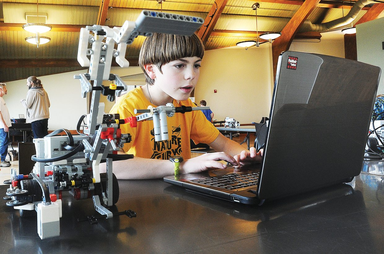 Christopher Stone, 11, works to program his robot during a meeting of the competitive robotics team at the Bud Werner Memorial Library. Children in third through 12th grades took part in a number of hands-on activities for children including programming EV3 and WeDo Robots, playing with a scratch coding website, tinkering with Arduinos (an open source electronics platform) and playing education video games.