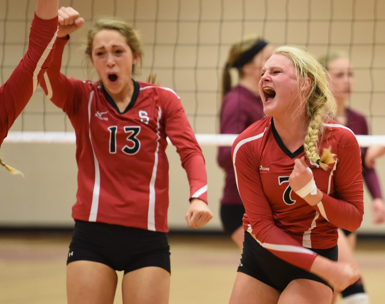 Maritza Wiedel, right, celebrates a big block Saturday during the regional volleyball tournament in Steamboat Springs.